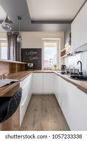 Modern kitchen with wooden worktop, white unit and blackboard