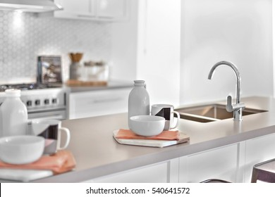 Modern kitchenware and utensils including mugs and cups with napkins near white bottles beside tap and sink on the counter top, background is blurred and white with the sunlight