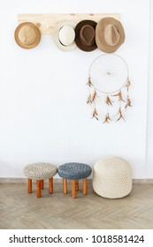 Modern knitted pouf and stools in a light interior, a wooden hanger with hats on the wall, dream catcher in a stylish interior