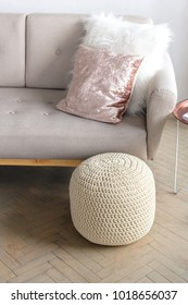 modern knitted pouf in a stylish interior,   pouf next to the sofa with pillows
