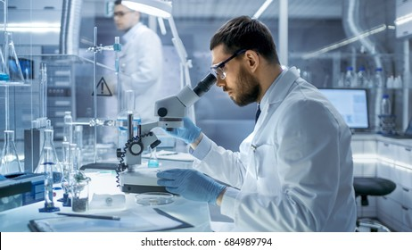In a Modern Laboaratory Research Scientist Examines Substance Under Microscope.