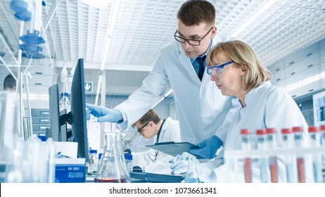 In Modern Laboratory Senior Female Scientist Has Discussion with Young Male Laboratory Assistant. He Shows Her Data Charts on a Clipboard, She Analyzes it and Enters It into Her Computer.