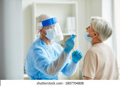 Modernes Laborpersonal mit persönlicher Schutzausrüstung, das ältere Frau auf Coronavirus mittels nasaler Abwaschverfahren untersucht