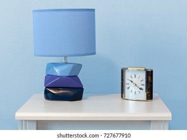 A modern lamp and a classic alarm clock on a white wooden nightstand