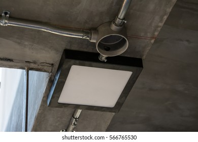 Modern lamp with metal pipe under the concrete ceiling