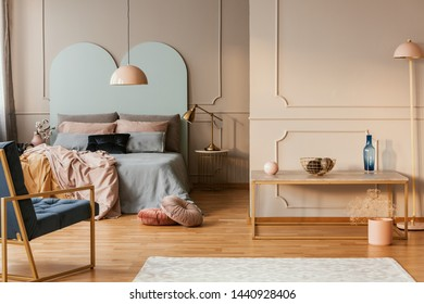Modern lamp on nightstand table next to king size bed in grey bedroom interior