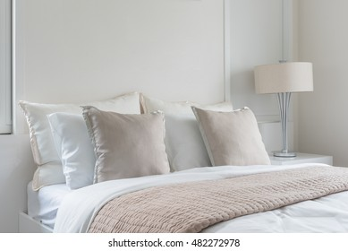 modern lamp on table side with picture frame on wall in bedroom design