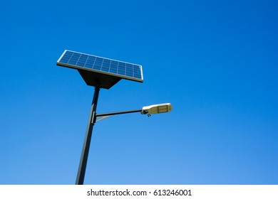 Modern lamp and solar photovoltaic panel - street lighting using renewable energy of sun to produce electricity for creating light. Clear blue sky in the background (copy space composition)