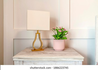 Modern lampshade and potted plant with flowers on the wooden side table