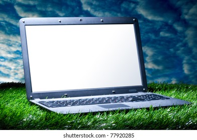modern laptop with blank screen on grass outdoors