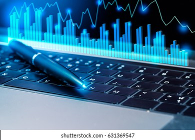Modern laptop computer with Black ink pen and business investment graphs.Investment Profit information data.success invest ,technology and big data concept.