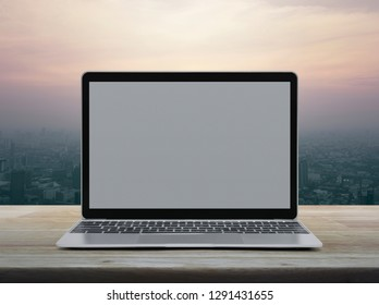 Modern laptop computer with blank grey screen on wooden table over office city tower and skyscraper at sunset sky, vintage style