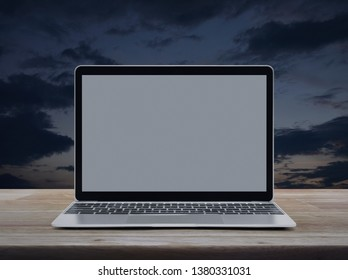 Modern laptop computer with blank grey screen on wooden table over sunset sky