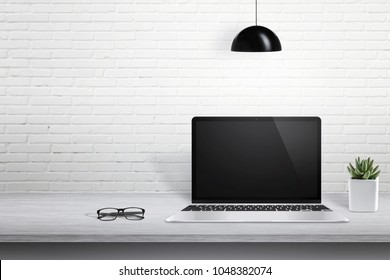 Modern laptop computer on desk with blank screen for mockup. White brick wall in background with free space for text.
