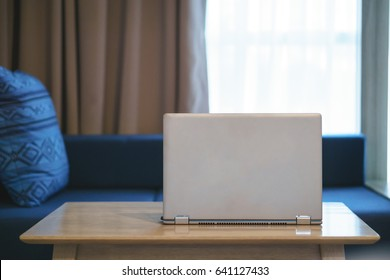 Modern laptop computer on wooden table in residential room