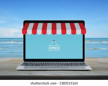 Modern laptop computer with online shopping store graphic and open sign on wooden table over tropical sea and blue sky with white clouds, Business internet shop online concept