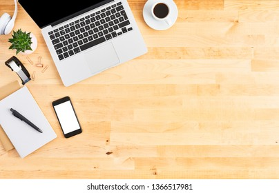 Modern laptop computer. Top view of wooden office desk with laptop computer, smartphone, notebook, headphone, plant and cup of coffee. Modern office. Copy space for text.