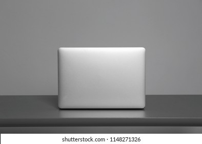 Modern laptop on table against gray background