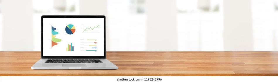 Modern laptop on wooden table showing charts and graph against office with white wall and windows indoor background bokeh light, Analysis Business, Statistics Concept. Banner