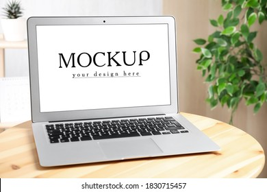 Modern laptop with text Mockup Your Design Here on screen