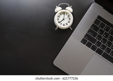 Modern laptop with white clock on wooden table .work and time concept