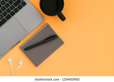 Modern laptop, white headphones, gray notebook with a pen and a cup of coffee on the orange background and a place for text, a view from above. Flatlay Copyspace.