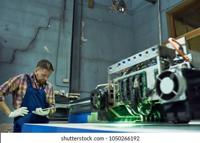 Modern laser engraving equipment in industrial workshop, machine processing glass with operator in background, copy space
