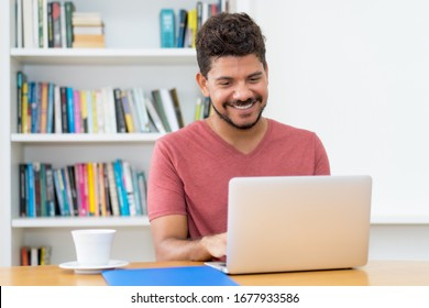 Modern latin american man with beard working at computer at home