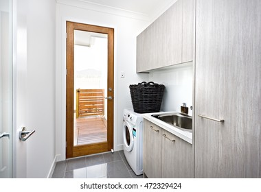 Modern laundry room with grey cupboards on the wall near a wooden door with a glass panel closed, there is a black basket made in rattan on the washing machine