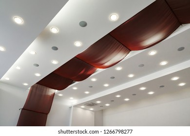 Modern layered ceiling with embedded lights and red cloth.