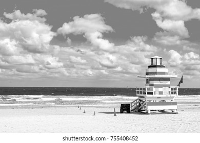 modern life guard house or beach patrol tower white and red color on ocean or sea water coast with sand and cloudy sky, copy space, black and white