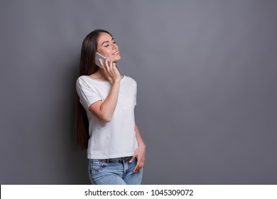 Modern lifestyle and communication. Smiling beautiful brunette girl talking on phone while standing on gray studio background with copy space