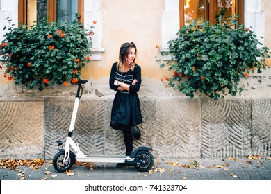 Modern lifestyle details, happy girl with flowers in urban city enjoying the electric scooter. Happiness and carefree concept