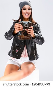Modern Lifestyle Ideas. Open Happy Caucasian Brunette in Black Leather Jacket Posing With Old School Film Photocamera. Against White.Focus on camera. Vertical Image Orientation