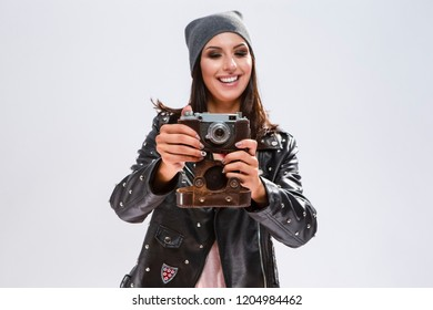 Modern Lifestyle Ideas. Open Happy Caucasian Brunette in Black Leather Jacket Posing With Old School Film Photocamera. Against White.Focus on Camera. Horizontal Image Composition