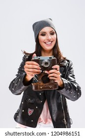 Modern Lifestyle Ideas. Open Happy Caucasian Brunette in Black Leather Jacket Posing With Old School Film Photocamera. Against White.Focus on camera. Vertical Image