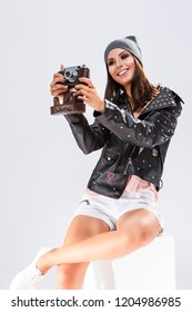 Modern Lifestyle Ideas. Open Happy Caucasian Brunette in Black Leather Jacket Posing With Old School Film Photocamera. Against White.Vertical Image Composition