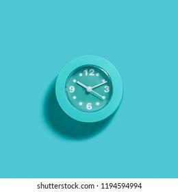 Modern light blue alarm clock on light blue background. Minimal monochrome concept