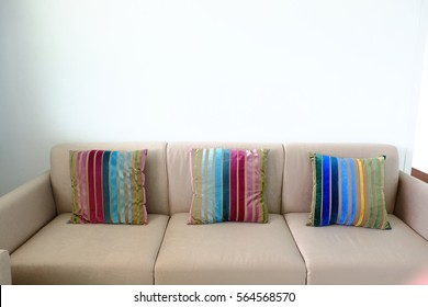 Modern light brown sofa with white wall and colorful pillows