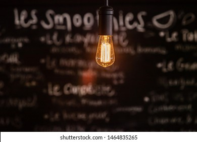 Modern light bulb in eco-friendly bistro. A closeup shot of a shining lightbulb inside a smoothie bar, chalkboard menu is seen blurred out in background with copy space below the light.
