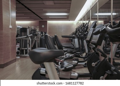 Modern light gym. Sports equipment in gym. Barbells of different weight on rack.