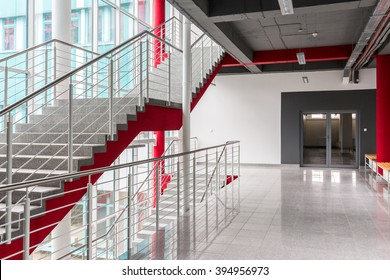 Modern, light staircase with silver railing, red details and black ceiling