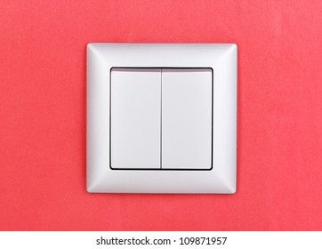 Modern light switch on red background