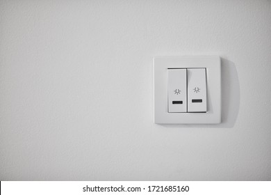 Modern light switch on a white wall.