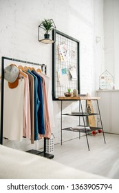 Modern light teenage bedroom with straight rack and pinboards