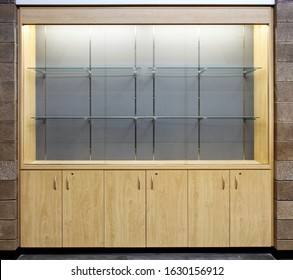 A modern, lighted display cabinet, with tempered glass shelving, for showing trophies from the achievements of school sports teams.