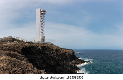 The modern lighthouse of Buenavista on the north side of the Atlantic island of Tenerife in sunshine. He is standing on a rock by the sea. Behind it is a banana plantation.