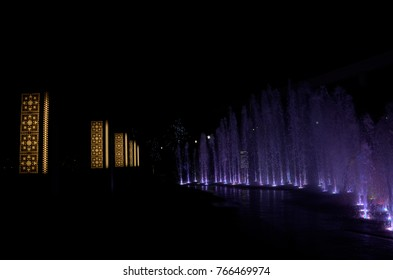 Modern lit night fountain illuminated blue and purple color on dark background.