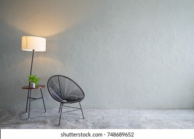 Modern living room with black leisure chair ,green plant and lamp stand. cement floor and concrete wall , Interior design with Loft style .