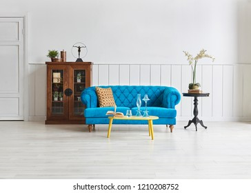 Modern living room blue armchair and white classic pattern wall. Wooden cabinet black coffee table and home decoration.